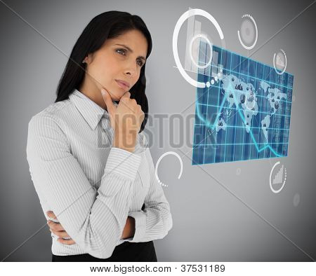 Business woman looking at world map hologram on grey background