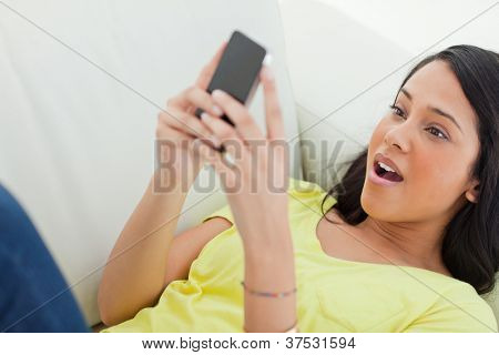 Close-up of a surprised Latino looking her smartphone while lying on a sofa