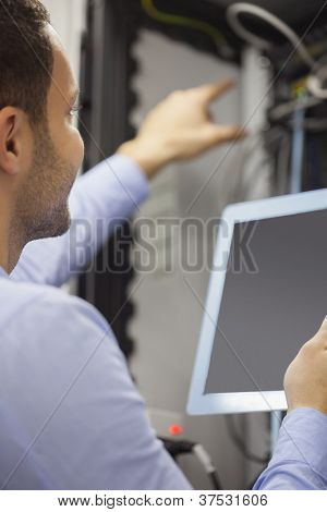 Man fixing wires with tablet pc in data center