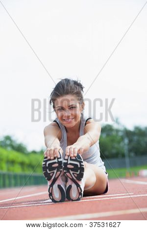 Smiling woman stretching legs on track