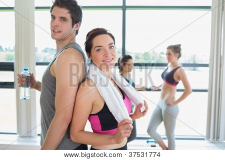 Man and woman standing back to back at the gym smiling