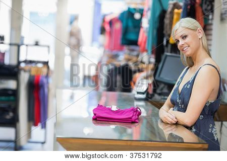 Woman smiling behind counter with folded clothes in clothing store
