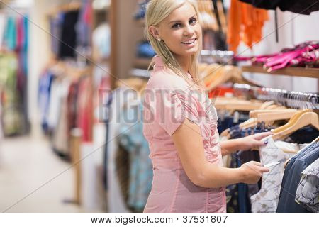 Woman standing at the clothes rack and smiling in shopping mall