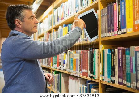 Man putting a tablet pc in the shelves in the library