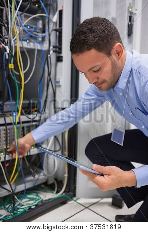 Man using tablet pc to work on servers in data center