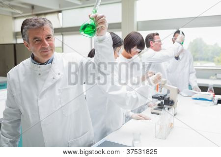 Chemist raising beaker of green liquid in busy lab