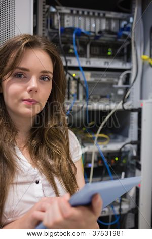 Woman with tablet pc standing in front of servers in data center