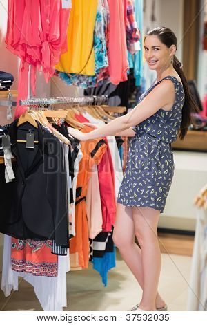 Woman is standing at a clothes rack smiling in the shop
