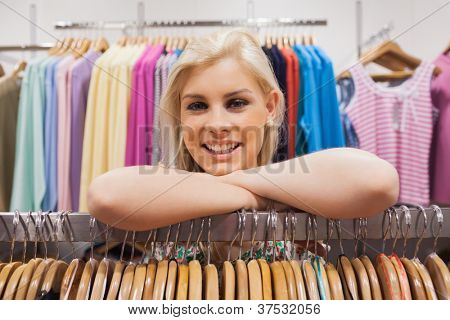 Woman leaning on clothes rack of a boutique smiling