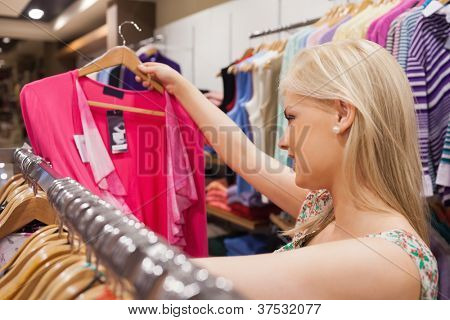 Woman looking at clothes in a boutique while standing at a clothes rack