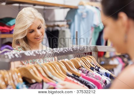 Woman looking at the clothes rack and smiling with friend