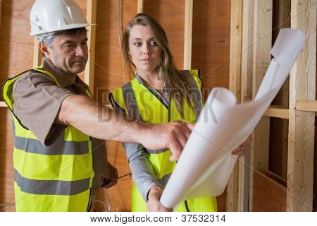 Two architects checking blueprints in consttuction site