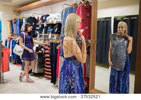 Woman standing in front of mirror holding up shirt in clothing store