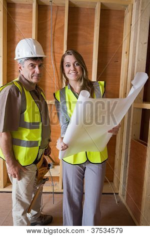 Smiling architects holding blueprints in construction site