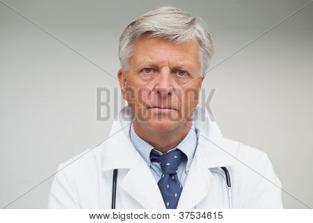 Mature doctor looking looking serious wearing lab coat