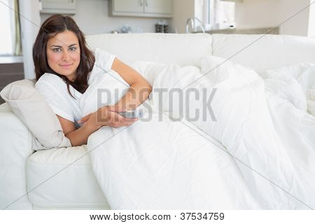 Woman relaxing on the sofa and holding a remote while watching television