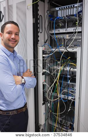 Smiling man standing in front of servers in data center