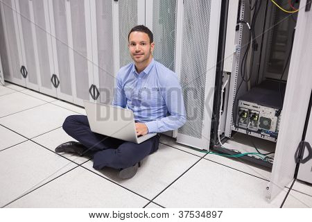 Man sitting on floor beside servers with laptop in data center