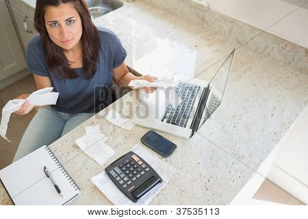 Young woman calculating bills and looking worried in kitchen