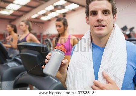 Happy man drinking sports drink in gym