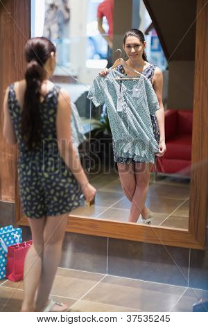 Woman is smiling and holding up clothes at the clothes store
