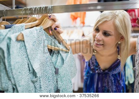 Woman  standing at the clothes rack smiling