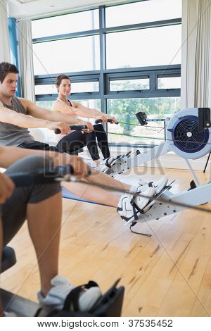 Woman looking up from rowing machine workout in fitness studio