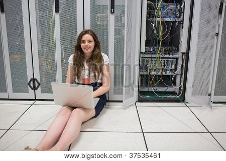 Woman checking the servers with laptop sitting on the floor in data center