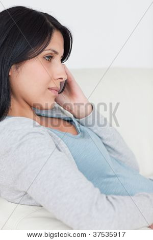 Woman with a phone in her hand while sitting on a couch in a living room