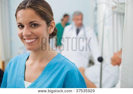 Lächelnd Krankenschwester im Krankenhauszimmer mit Arzt, Patient und andere Krankenschwester im Hintergrund