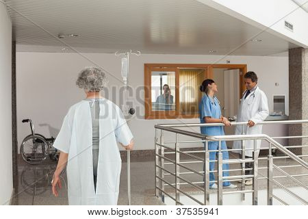 Old woman walking along the hallway in a hospital with a drip in her hand