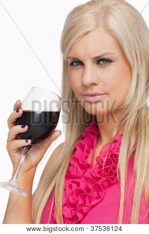 Serious blonde drinking a glass of red wine against white background