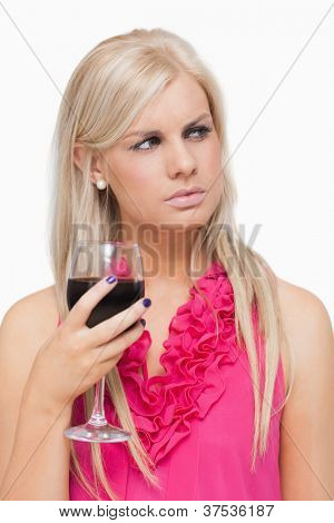 Blonde holding a glass of red wine against white background