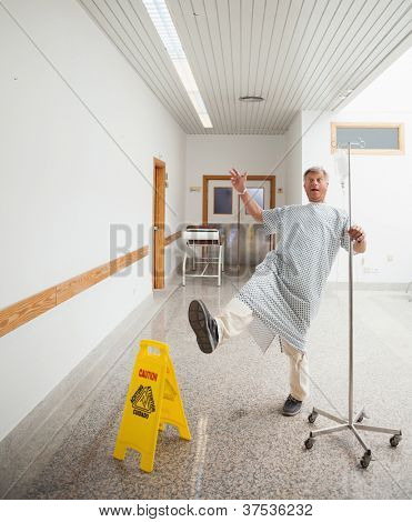 Patient pretending to slip on wet floor in hospital corridor
