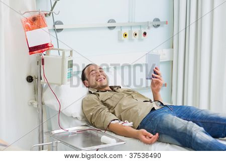 Smiling transfused patient looking at a tablet computer in hospital ward