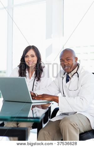 Smiling doctor working hard on a laptop while accompanied by his co-worker