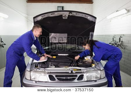 Mechanics examining a car engine in a garage