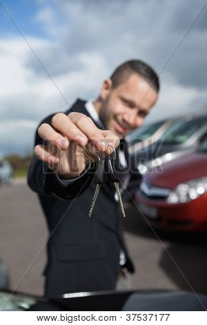 Happy businessman holding car keys outdoors
