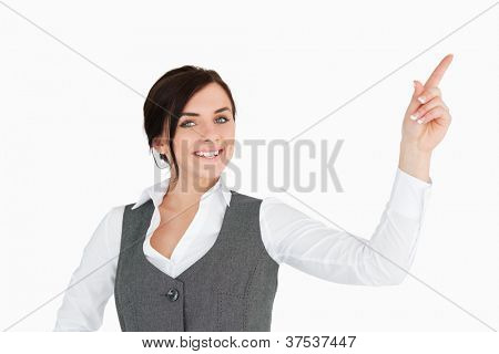 Smiling well-dressed brunette pointing up against white background
