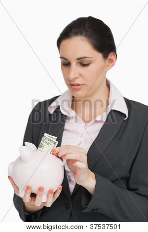 Brunette putting dollars into a piggy-bank against white background