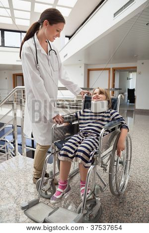Female doctor smiling at child in wheelchair and neck brace in hospital corridor