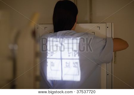 Radiography being done on a patient in an examination room