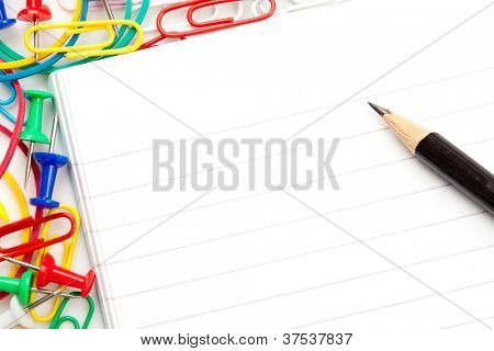 Notepad with large group of muti coloured stationery and a pencil against a white background