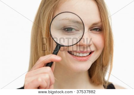 Woman placing a magnifying glass on her eye against white background
