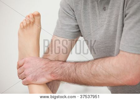 Close-up of a physiotherapist manipulating an ankle in a room