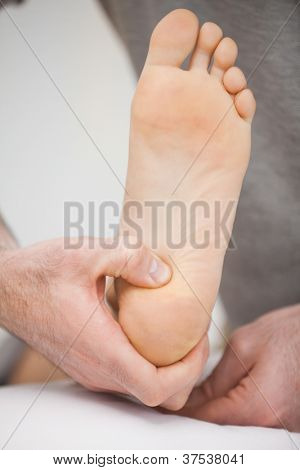 Foot being raised by a chiropodist in a room