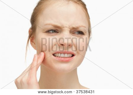 Woman massaging her cheek against white background