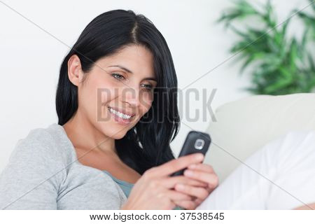 Woman holding a phone with two hands while sitting on a couch in a living room