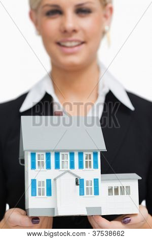 Smiling businesswoman holding a model house against white background