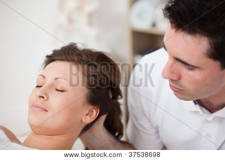 A doctor massaging the head of his patient while holding it in a room